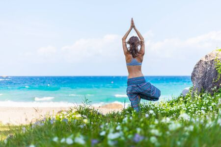 Young woman performs yoga exercises on a green lawn with sea on the background Фото со стока