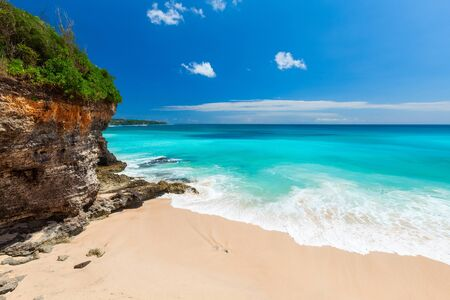 Balinese sandy beach with green steep cliff and torquoise water. Bali, Indonesia