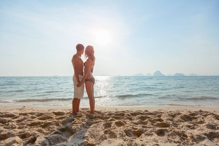 Young couple stand on the tropical beach. Man and woman standing together and enjoying pleasant weather on the beach