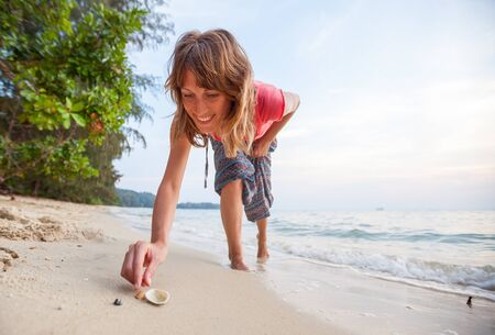 Young happy woman collects shells on the tropical beach Фото со стока