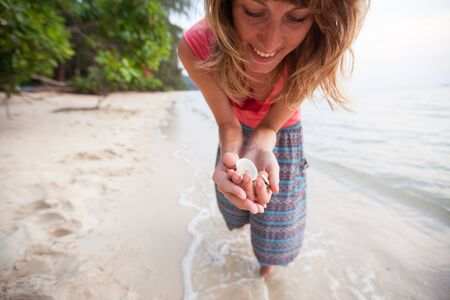 Young happy woman collects shells on the tropical beach. Focus on the shells