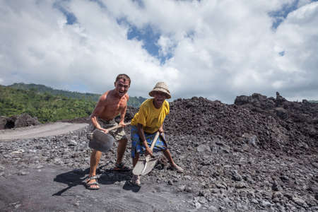 KINTAMANI, BALI, INDONESIA MAY 19, 2012: Balinese man with spade and foreigner with hoe have fun on a lava field in Indonesia