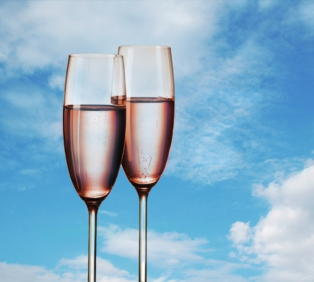champagne flutes: Two glasses of pink champagne, on background of sky