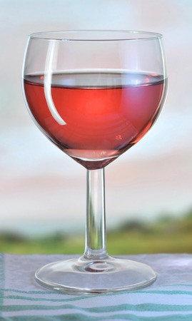 Glass of pink wine on garden table in evening, shallow depth of field