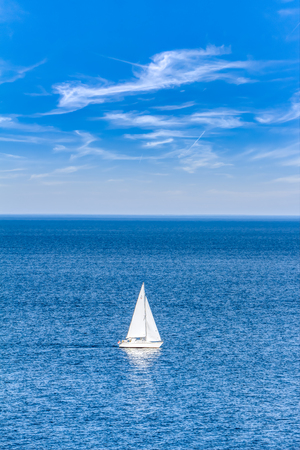Blue open water with a sailboat in summer