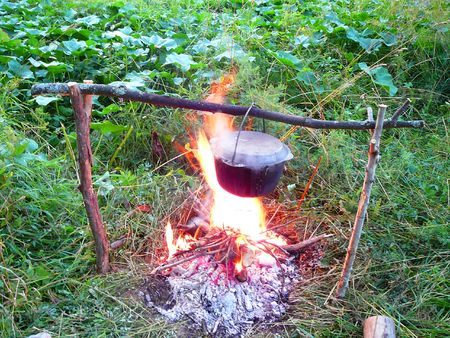 soup kettle: black iron kettle with boiling soup over the campfire