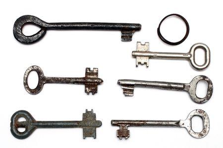 six old rusty keys and keyring isolated on white photo