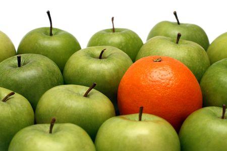 different concepts - orange between green apples Stock Photo