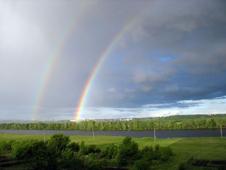 landscape with rainbow over lake after storm Stock Photo
