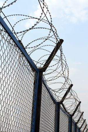 wire: fence with barbed wire under blue sky