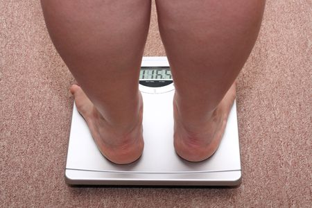 abstinence: women legs with overweight standing on bathroom scales Stock Photo
