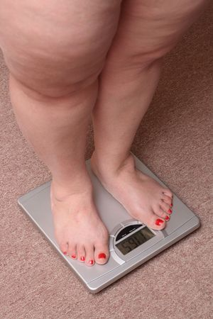 women legs with overweight standing on bathroom scales Stock Photo
