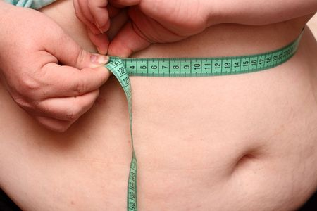 overweight women measure her stomach Stock Photo