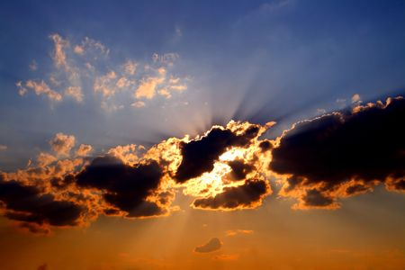 sun rays behind dark clouds in sky before sunset Stock Photo - 3048914