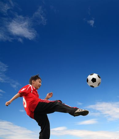 asian boy playing football under blue sky Stock Photo