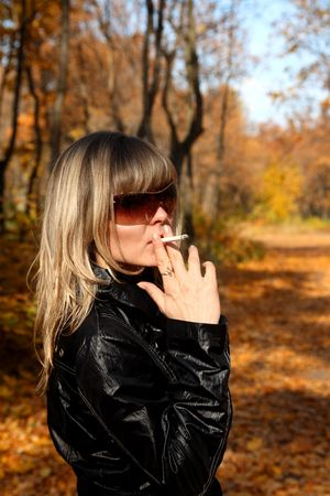 beautiful young girl with cigarette in autumn park photo