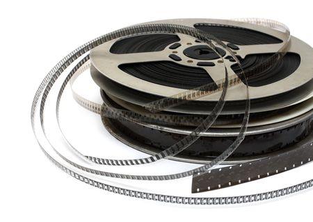 stack of old movie films on metal reel on white