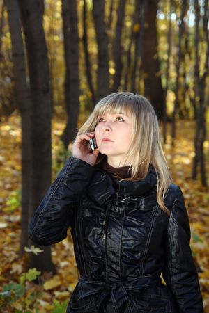 converse: beautiful young woman talking by phone in autumn park