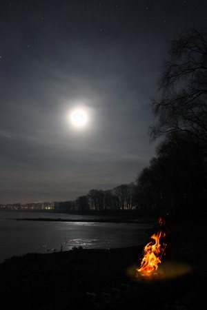 night landscape with bonfire flame and moon over lake
