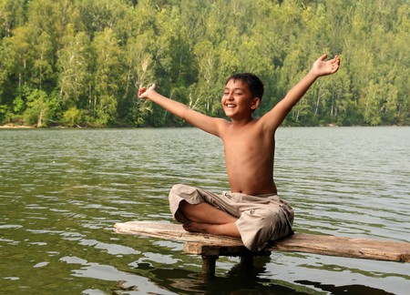 happy asian boy with hands up on stage in lake photo