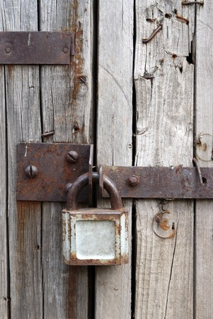 old rusty padlock on wooden door of old shed