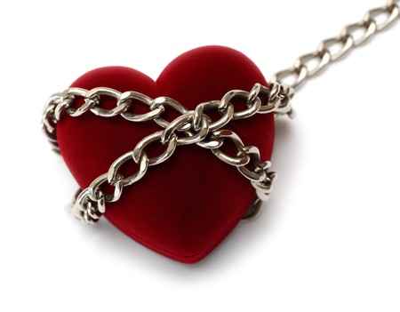 forbidden love: red heart locked with chain isolated on white