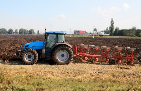 the plough: agriculture tractor with plough in field Stock Photo