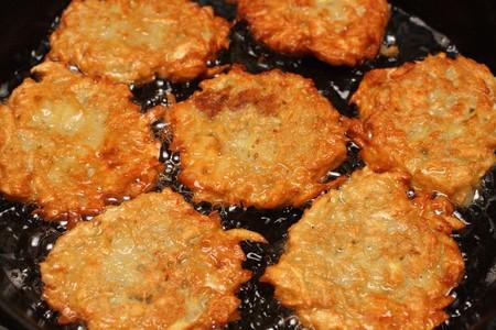 potato pancakes frizzle in black frying pan Stock Photo