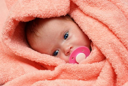 teat: newborn baby with soother in peachey blanket Stock Photo