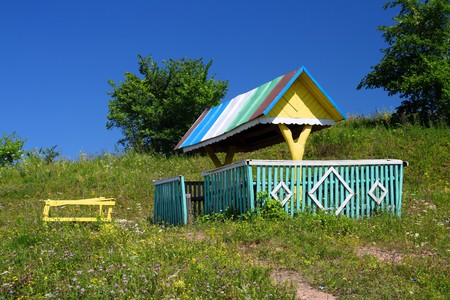 rustic arbour with well on summer hill photo