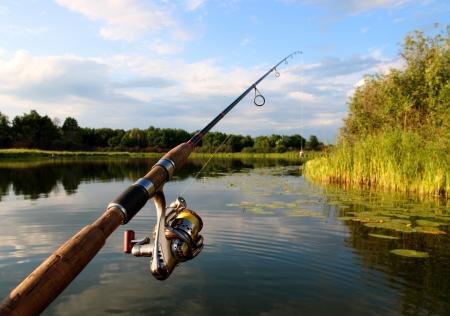 pescador: hilado con carrete y el verano lago