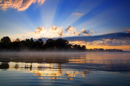 sunrise with sunbeams and clouds and reflection in river Stock Photo - 4707998