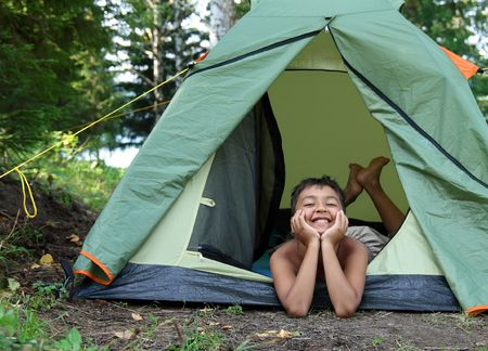 camping site: happy boy in camping tent in summer forest Stock Photo
