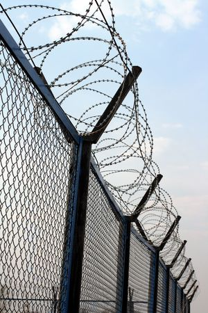 fence with barbed wire under blue sky Stock Photo - 4718603