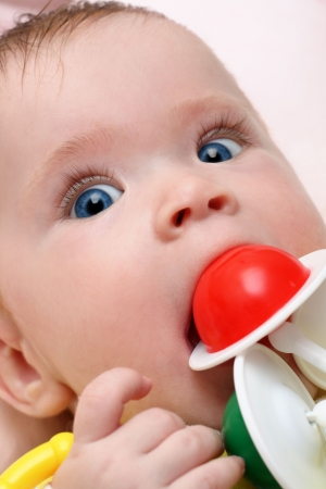 baby girl biting rattle close-up portrait