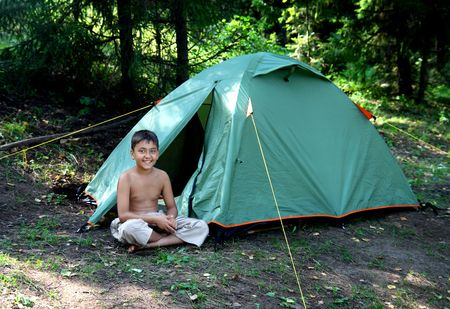 smiling boy near camping tent in summer forest photo