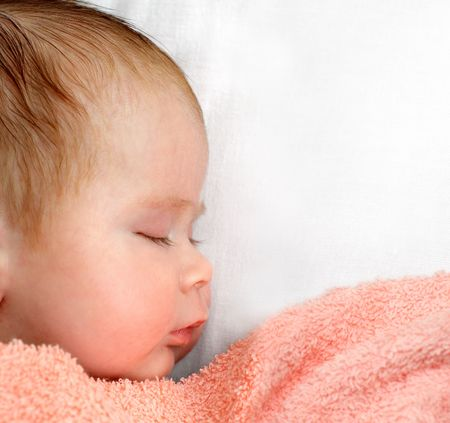 newborn baby sleeping under peachey blanket photo