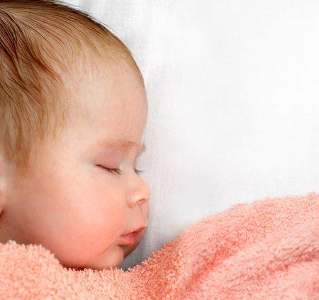coverlet: newborn baby sleeping under peachey blanket