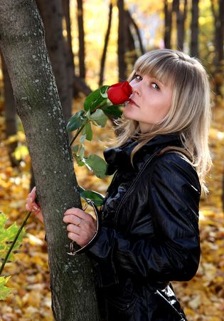 lifestile: beautiful young girl with rose in autumn park