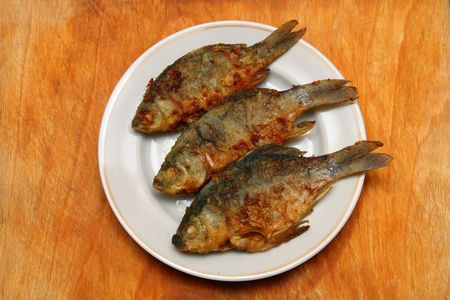 crucian: fried fish crucian in plate on wooden table Stock Photo