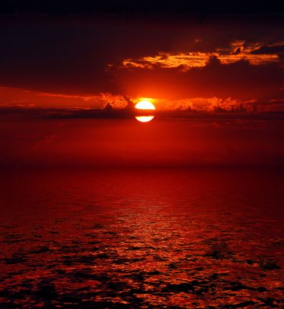 dramatic bloody sunrise on dark sky over sea Stock Photo - 5823364