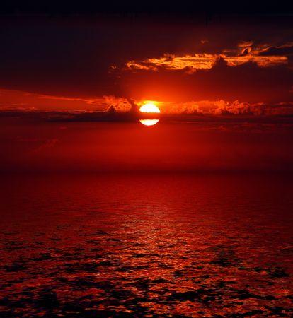 dramatic bloody sunrise on dark sky over sea photo
