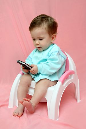pocket pc: baby with pocket PC sitting on chamber-pot Stock Photo