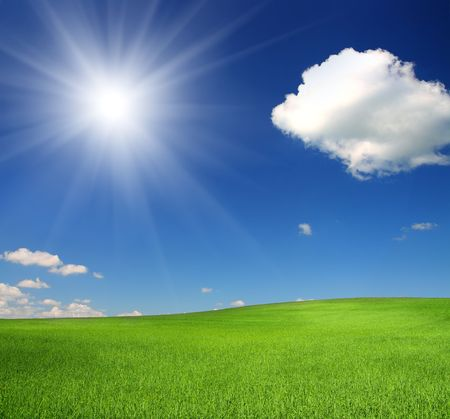 green hill with wheat under blue sky with sun photo