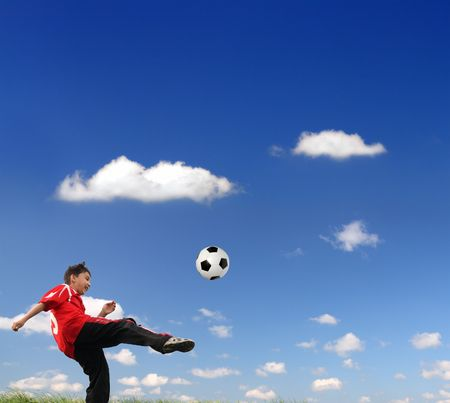 junior soccer: asian boy playing football under blue sky Stock Photo