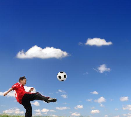jugando futbol: Asian ni�o jugando al f�tbol bajo cielo azul Foto de archivo