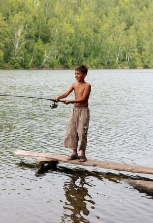 boy fishing with spinning on stage in lake photo