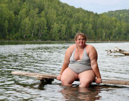 mujer gorda: mujer sentada en el escenario en el lago de sobrepeso
