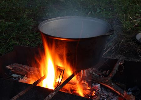 soup kettle: kettle with boiling soup over campfire in dusk Stock Photo