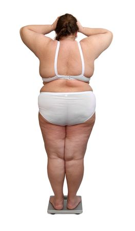 large build: women with overweight in underwear from behind on scales
